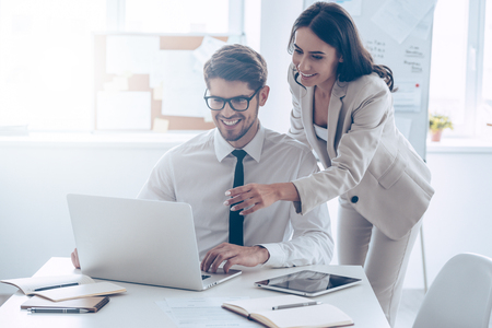 Foto de We already have great results! Young beautiful woman pointing at laptop with smile and discussing something with her coworker while standing at office - Imagen libre de derechos