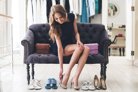 Foto de That is perfect pair! Beautiful young woman trying on high heel shoes while sitting on sofa at the shoe store - Imagen libre de derechos