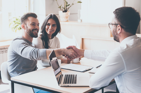 Photo for Good deal! Cheerful young man bonding to his wife while shaking hand to man sitting in front of him at the desk - Royalty Free Image