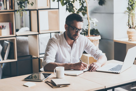 Photo for Making some notes. Concentrated mature man writing something in note pad while sitting at his working place in office - Royalty Free Image