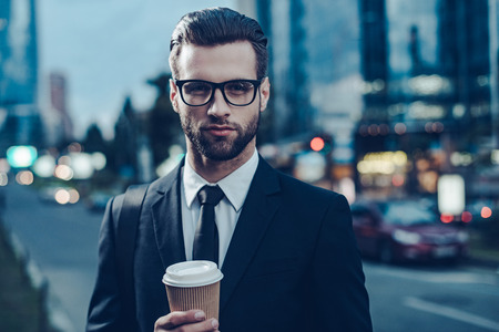 Night time image of confident young man in full suit holding coffee cup and looking at camera while standing outdoors with cityscape in the background