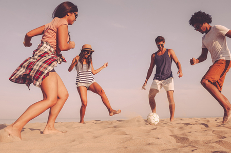 Photo for Just having fun. Group of cheerful young people playing with soccer ball on the beach with sea in the background - Royalty Free Image