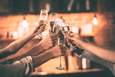 Foto de Cheers! Group of people cheering with champagne flutes with home interior in the background - Imagen libre de derechos