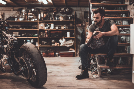 Photo pour Confident mechanic. Confident young man holding rag and looking at motorcycle while sitting near it in repair shop - image libre de droit