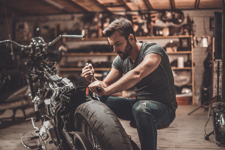 Photo pour This bike will be perfect. Confident young man repairing motorcycle in repair shop - image libre de droit