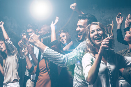 Foto de Dancing all night long. Group of beautiful young people dancing with champagne flutes and looking happy - Imagen libre de derechos