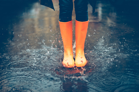 Photo pour Feeling protected in her boots. Close-up of woman in orange rubber boots jumping on the puddle - image libre de droit