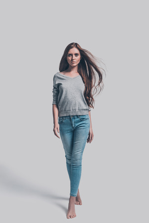 Photo for Confident and beautiful. Full length studio shot of attractive young woman in casual wear walking and looking at you - Royalty Free Image