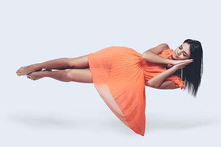 Foto de Sleeping beauty. Full length studio shot of attractive young woman in orange dress hovering in air and keeping eyes closed - Imagen libre de derechos