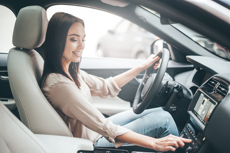 Photo pour Searching for favorite music. Young attractive woman smiling and pushing buttons while driving a car - image libre de droit