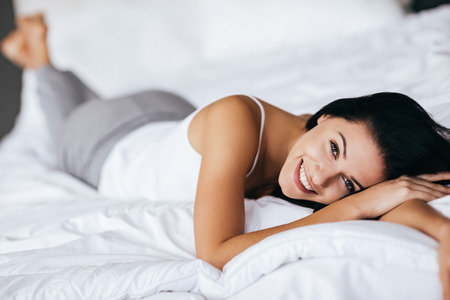 Photo for Natural beauty. Young woman looking at camera and smiling while lying on the bed at home - Royalty Free Image