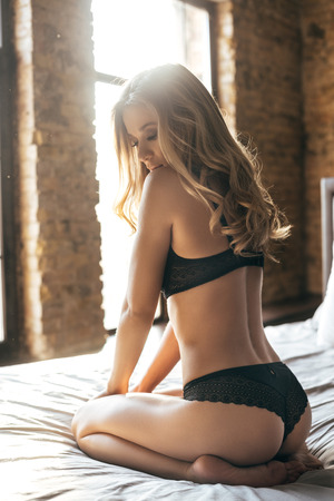 Photo for Time stops when you looking at her. Rear view of gorgeous young woman in black lingerie looking over her shoulder while sitting on bed at home - Royalty Free Image