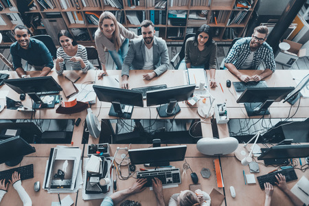 Foto de Young and successful. Top view of group of young business people in smart casual wear working together and smiling while sitting at the large office desk - Imagen libre de derechos