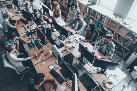 Foto de Confident business experts a work. Top view of group of young business people in smart casual wear working together while sitting at the large office desk - Imagen libre de derechos