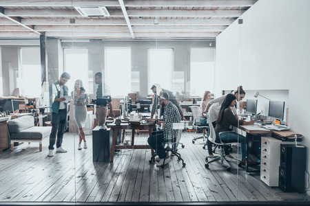 Foto per Team at work. Group of young business people in smart casual wear working together in creative office - Immagine Royalty Free