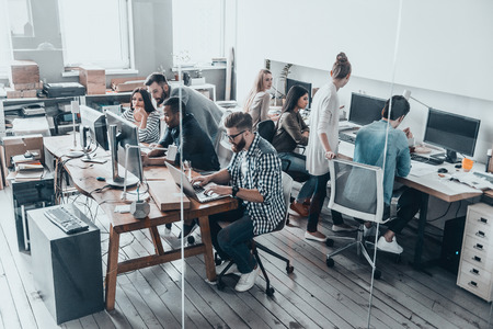 Photo for Confident and successful team.  Top view of young modern people in smart casual wear concentrating at their projects while working together behind the glass wall in creative office  - Royalty Free Image