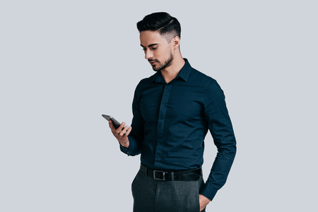 Photo pour Sending important business messages. Serious young man in shirt typing text message using his smart phone while standing against grey background - image libre de droit