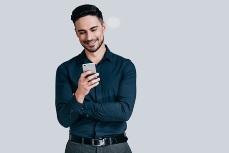 Photo pour Great news from friend. Handsome young man holding smart phone and looking at it with smile while standing against grey background - image libre de droit