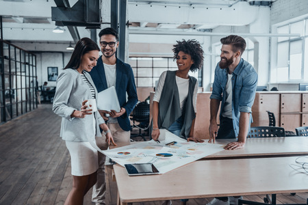Foto de Planning new business strategy. Group of young business people in smart casual wear working together and smiling while standing near the wooden desk in office - Imagen libre de derechos
