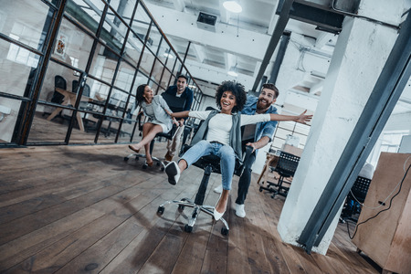 Photo for Work hard play hard! Four young cheerful business people in smart casual wear having fun while racing on office chairs and smiling - Royalty Free Image