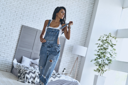Photo for Irresistible girl. Attractive young woman touching her bib overalls and looking away while walking in the bedroom at home - Royalty Free Image