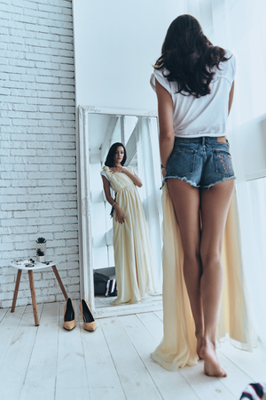 Foto de Amazing dress! Full length rear view of attractive young woman trying on her dress while looking in the mirror at home - Imagen libre de derechos