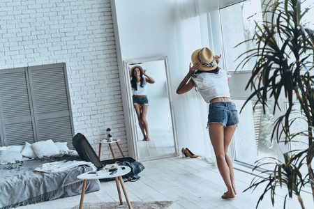 Photo for She is all about fashion. Full length rear view of young woman looking in the mirror while trying on her sun hat - Royalty Free Image