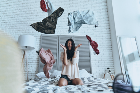 Photo pour Too hard to choose! Beautiful young woman sitting on bed and making face while clothing flying everywhere - image libre de droit
