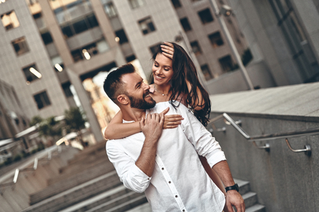 Foto de Making each other happy. Attractive young woman embracing her handsome boyfriend while spending time together in the city - Imagen libre de derechos
