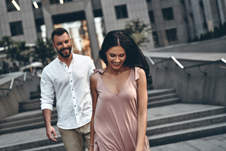 Foto de Amazed by her beauty. Beautiful young woman smiling while walking through the city street with her boyfriend - Imagen libre de derechos