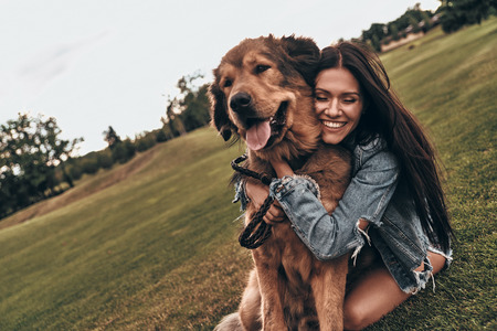 Photo for So cute and lovable. Beautiful young woman keeping eyes closed and smiling while embracing her dog outdoors - Royalty Free Image