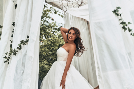 Photo for Attractive young woman in wedding dress keeping hand behind head and smiling while standing outdoors - Royalty Free Image