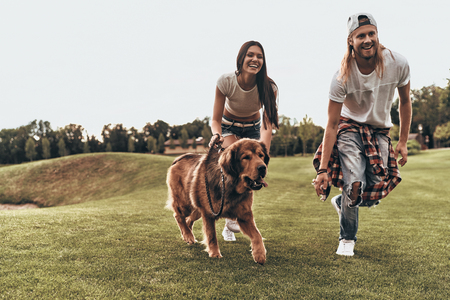 Photo pour Perfect furry friend.  Full length of beautiful young couple playing with their dog while running in the park - image libre de droit
