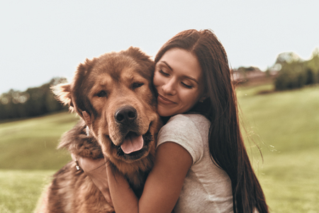Photo for Her best friend. Beautiful young woman keeping eyes closed and smiling while embracing her dog outdoors - Royalty Free Image