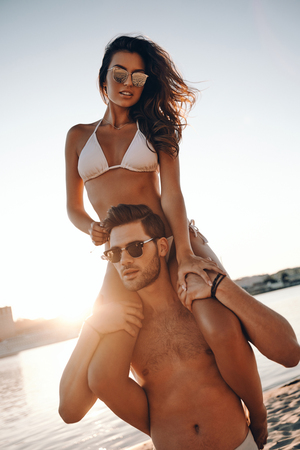 Photo for Living at the moment.  Handsome young man carrying his attractive girlfriend on shoulders while standing on the beach - Royalty Free Image