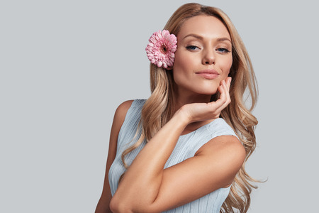 Foto de True feminine beauty. Attractive young woman with a flower in hair looking at camera and smiling while standing against grey background - Imagen libre de derechos