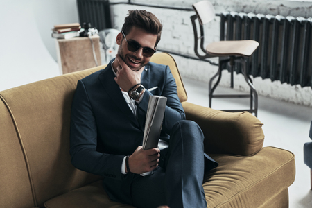 Photo for He got candid smile. Handsome young man in full suit keeping hand on chin and smiling while sitting on the sofa - Royalty Free Image