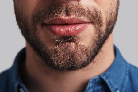 Foto de Real man.  Close up of young unshaved man standing against grey background - Imagen libre de derechos