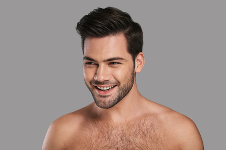 Foto de Fresh and handsome. Handsome young smiling man looking away while standing against grey background - Imagen libre de derechos