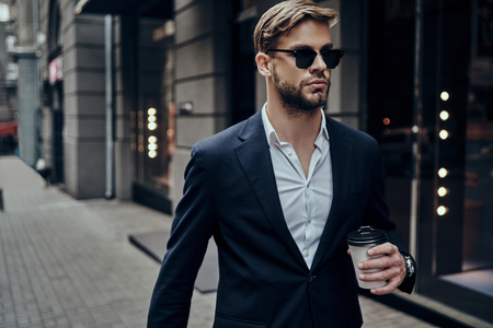 Photo pour Perfect businessman. Handsome young man in smart casual wear carrying disposable cup while walking through the city street - image libre de droit