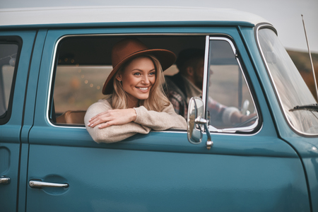 Photo pour Doing what they love. Attractive young smiling woman looking out the vans window while enjoying the car travel with her boyfriend - image libre de droit