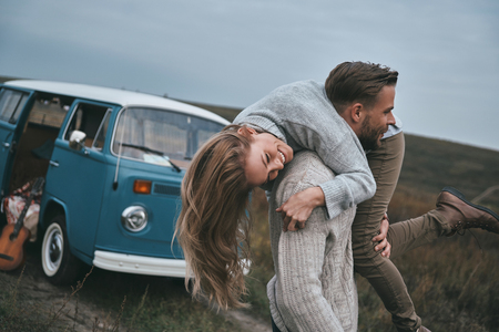Photo pour Crazy in love.  Handsome young man carrying his attractive girlfriend on shoulders and smiling while standing near the blue retro style mini van - image libre de droit
