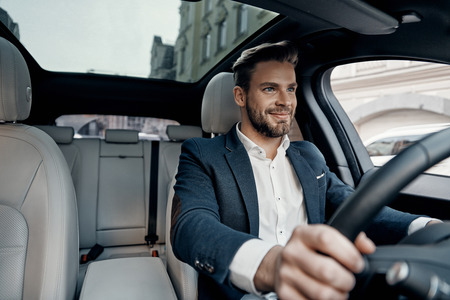 Photo for Success in motion. Handsome young man in full suit smiling while driving a car - Royalty Free Image