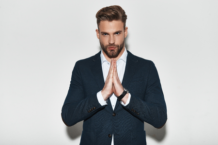 Photo for Confidence and charisma. Handsome young man in formalwear holding hands clasped and looking at camera while standing against grey background - Royalty Free Image