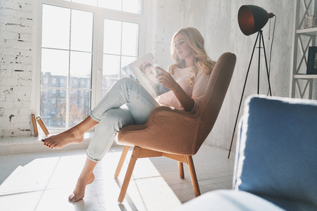 Photo for Beautiful young woman reading a magazine while sitting in the armchair at home - Royalty Free Image