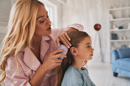 Photo for Taking care of her princess. Beautiful young mother brushing her daughters hair while sitting on the bed at home - Royalty Free Image