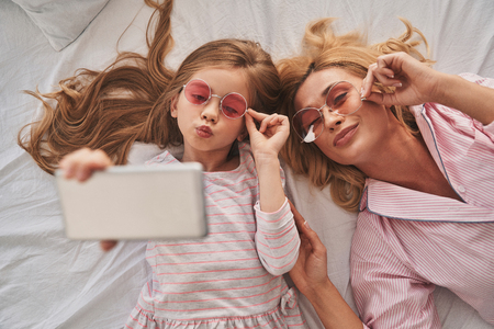 Photo for Perfect selfie. Top view of young beautiful mother and her cute daughter taking selfie with smart phone and smiling while lying on the bed at home - Royalty Free Image