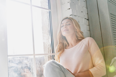 Photo for Feeling calm and happy. Attractive young woman keeping eyes closed and smiling while sitting on the window sill at home - Royalty Free Image