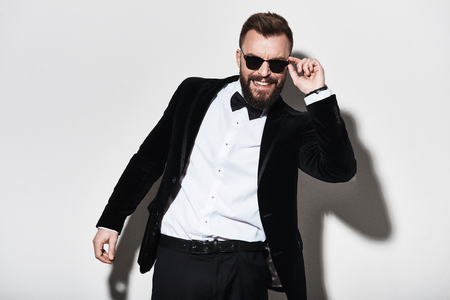 Foto de Man of charisma. Handsome young man in full suit adjusting his eyewear and smiling while standing against grey background - Imagen libre de derechos