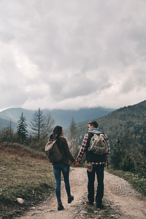 Photo for Full length rear view of young couple holding hands while hiking in mountains - Royalty Free Image